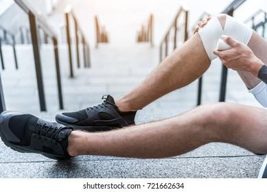 Man bandaging leg on floor outdoor