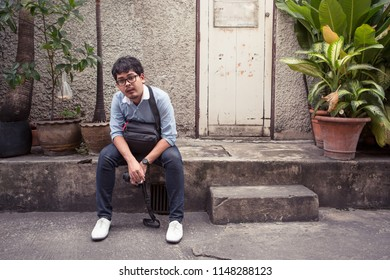 Man in Bangkok urban area sit in front of old classic slum style house. He hold DSLR camera like foreigner tourist.