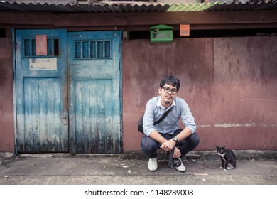 Man in Bangkok urban area sit with cat in front of old classic Chinese style house. He hold DSLR camera like foreigner tourist. Image contain space for copy text