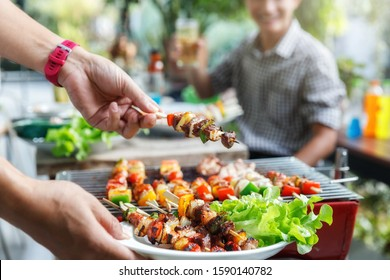 A man with a barbecue plate at a party between friends. Food, people and family time concept.