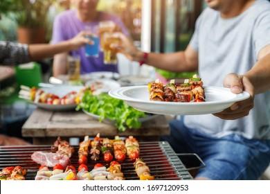 Ein Mann mit einem Grillteller auf einer Party zwischen Freunden. Essen, Menschen und Familienzeitkonzept.