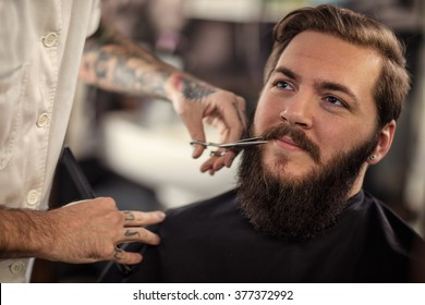 man barber with scissors cut the mustache smiling client