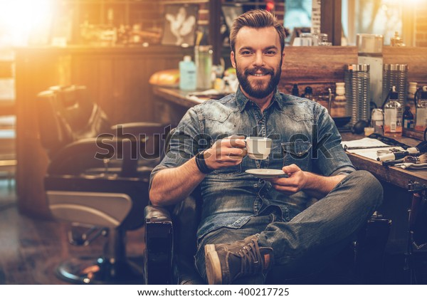 Man at barbershop. Cheerful young bearded man looking at camera and holding coffee cup while sitting in chair at barbershop