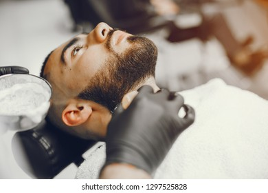 A man in a barbershop. Clipping beard in the barber. Rest in hairdressing salon