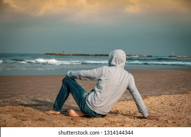 Man barefoot sitting on the beach and looking at the sea