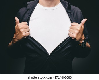 Man baring chest doing superman superhero pose revealing blank t-shirt with copy space