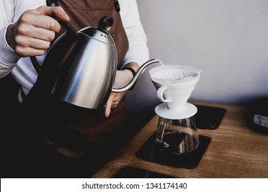 Man Barista in local cafe pouring water from the kettle into the coffee filter. Fresh morning pour over coffee blossoms in the dripper. Cooking, preparing education, master class from expert