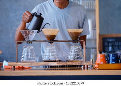 Man Barista to make a drip brewing, filtered coffee in a coffee shop.