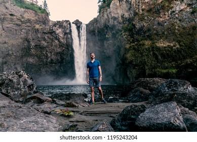 man at base of waterfall looking up.