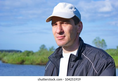 man in a baseball cap on the River