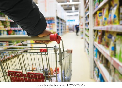 A man with a basket walks in a supermarket. Hand and part of the basket in focus, blurred background