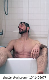 Man in bath tub wet skin head tilted back with eyes closed.