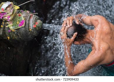 Man bathing holy spring water at Tampaksiring, Tirta Empul Temple in Bali, Indonesia.