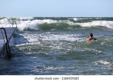 A man bathing at Kallbadhuset in Visby, Gotland Sweden.