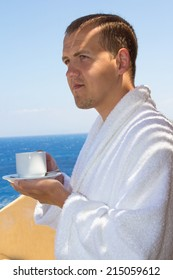 man in bathrobe with cup of coffee standing at terrace with sea view