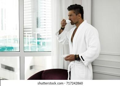 man in bathrobe drinks coffee in luxury hotel in the morning