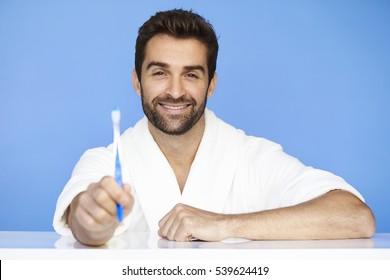 Man in bathrobe holding toothbrush, portrait