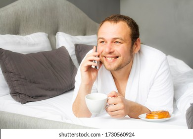 A man in a bathrobe is lying in a white bed drinking coffee and talking on the phone. Muzhchina on a business trip at the hotel.