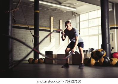 Man with battle ropes in gym