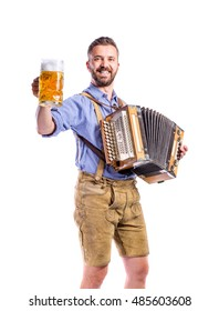 Man in bavarian clothes holding beer, playing accordion. Oktober