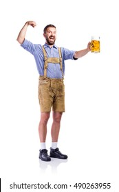 Man in bavarian clothes, holding beer, showing biceps