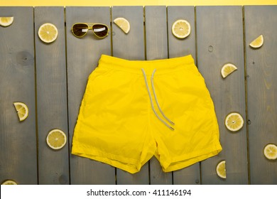 man beach accessories on wooden background. Yellow Swim Trunks, aviator sunglasses between parts of lemons on grey wooden board.