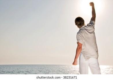 Man at the beach rising the hand