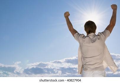 Man at the beach rising hands