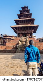 A man in a beanie standing in front of a temple in Bhaktapur, Nyatapola Temple. The Hindu temple has five stories. Discovering new cultures. A place of religious and historical worship. Spirituality