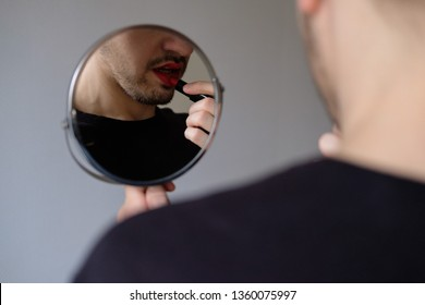 Man with a beard applying red lipstick on hisself. Doing makeup. Looking to a mirror close-up. Lgbt community. Transsexual guy.