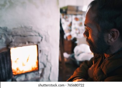 A man with a beard basking near village old Russian stove. Pensive old man. Dreams, looking at the fire in the fireplace. The life of the poor. An unhappy man. Toned