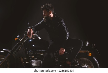 Man with beard, biker in leather jacket lean on motor bike in darkness, black background. Biker culture concept. Macho, brutal biker in leather jacket stand near motorcycle at night time, copy space.