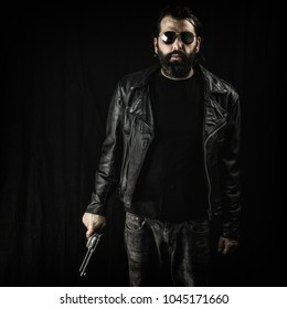 Man with a beard in a black leather jacket, wearing sunglasses and holding a gun.
