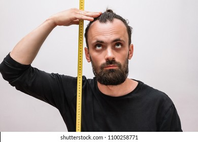 a man with a beard and a black t-shirt makes measurements with a tape measure