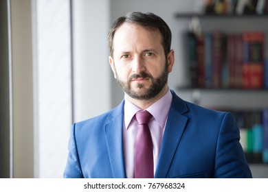 Man with beard in blue jacket, shirt and tie. Businessman or director pose in office. Career, profession, work. Fashion, style, dress code. Business, entrepreneurship concept.