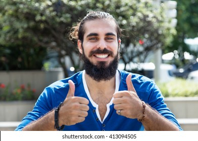 Man with beard and blue shirt showing both thumbs in city
