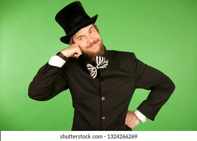 Man with a beard and a bow tie in a top hat listening with a smile