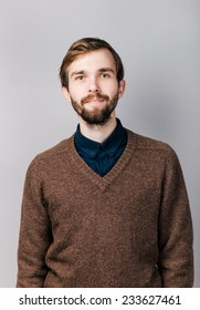 a man with a beard in brown sweater