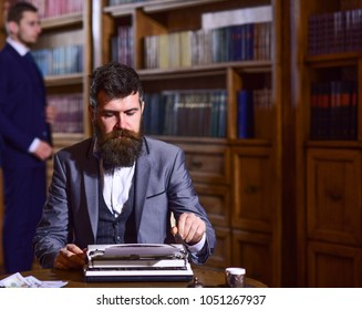 Man with beard and busy face sit in library and work with typewriter. Writer working on new book with friend and bookshelves on background. Author types novel or poem. Writing and literature concept.