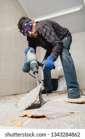man with a beard in a checkered shirt destroys the floor tiles with a construction puncher. Bottom view
