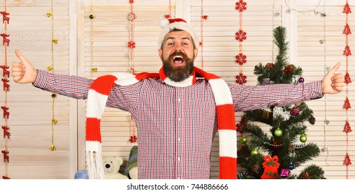 Man with beard in checkered shirt. Guy in red and white scarf puts hands wide. Santa Claus with happy face near wooden wall and Christmas tree on background. Celebration and New Year party concept.