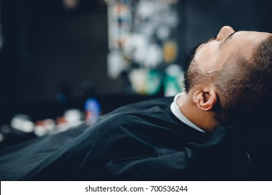 A man with a beard a client in a barbershop hairdresser on a shaving with a dangerous razor.