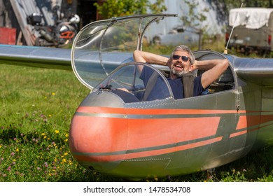 A man with a beard in the cockpit of a glider. Smiling glider pilot sitting in the cockpit. Pilot in dark sunglasses, denim shorts, a blue shirt and a sweater on the airfield after landing.