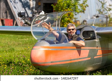 Man with a beard in the cockpit of a glider. Smiling sport glider pilot sitting in the cockpit. Pilot in sunglasses, denim shorts, a blue shirt and a sweater at the airfield after lucky landing.