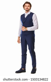 man with beard and dark hair stands on a white background in dark blue waistcoat and classic trousers with white shirt, he has a gold watch on his arm and blue sueded shoes looking in left direction