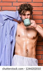 Man with beard drink coffee brick wall background. Guy hold tea or coffee cup. Macho sexy torso enjoy coffee. Athlete sleepy face tousled hair wear bathrobe hold mug. Morning coffee concept.
