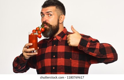 Man with beard drinks tomato juice isolated on white background. Guy with homegrown harvest shows thumbs up. Farming and autumn concept. Farmer with confused face uses cherry tomatoes stem as straw