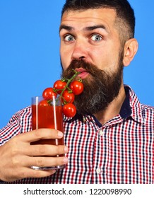 Man with beard drinks tomato juice isolated on white background. Farming and gardening concept. Farmer with surprised face pretends to use bunch of cherry tomatoes as straw. Guy with homegrown harvest