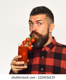 Man with beard drinks tomato juice isolated on white background. Farmer with surprised face pretends to use bunch of cherry tomatoes as straw. Farming and autumn concept. Guy holds homegrown harvest