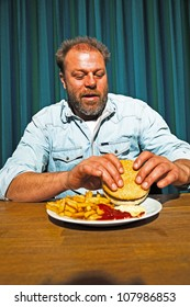 Man with beard eating fast food meal. Enjoying french fries and a hamburger.